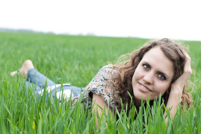 Портрет романтичного, молодая женщина при короткие волосы лежа на зеленой траве, мечтах стоковая фотография