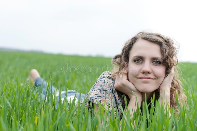 Портрет романтичного, молодая женщина при короткие волосы лежа на зеленой траве, мечтах стоковые фото