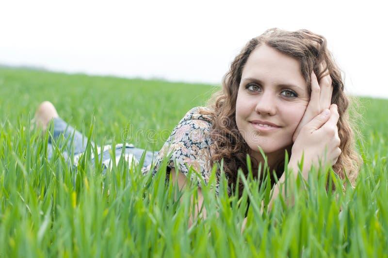 Портрет романтичного, молодая женщина при короткие волосы лежа на зеленой траве, мечтах стоковые изображения