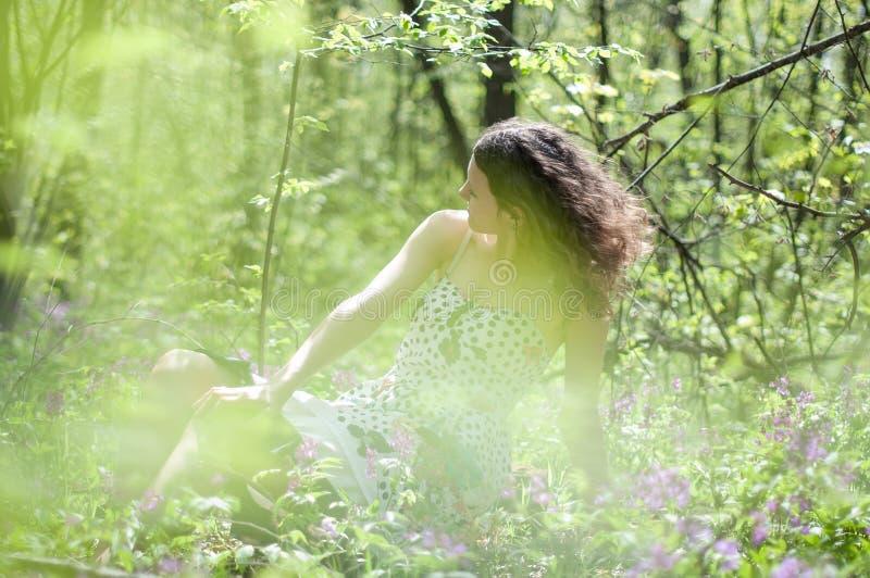 Портрет романтичного, молодая женщина при короткие волосы лежа на зеленой траве, мечтах стоковое изображение