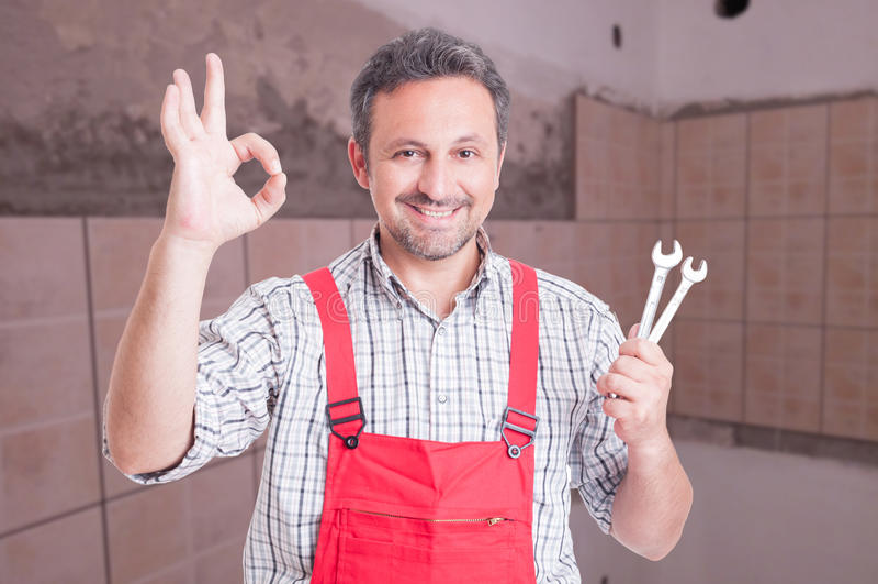 Портрет дружелюбного ремонтника делая о'кеы жест стоковое фото rf