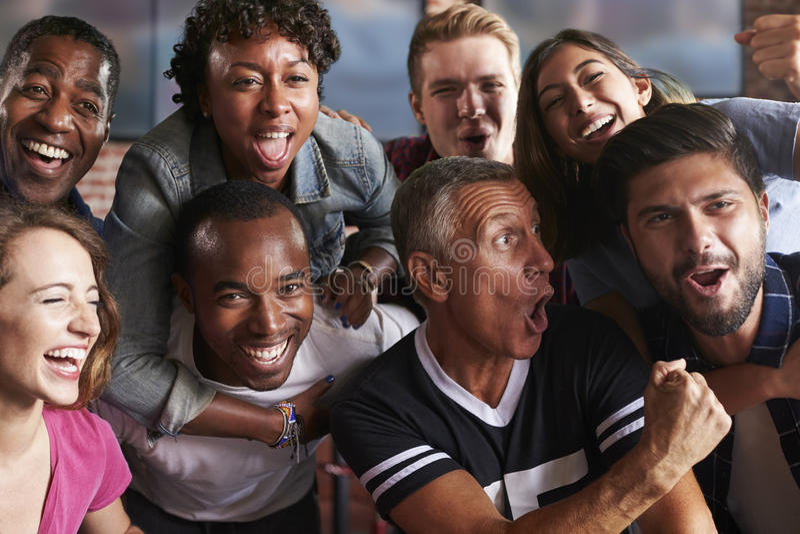 Портрет друзей наблюдая игру в баре спорт на экранах стоковое изображение