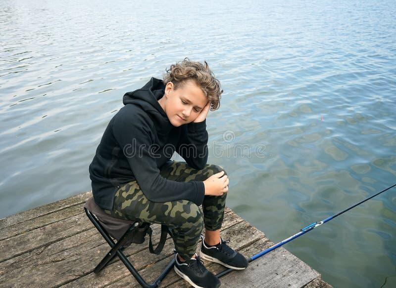Портрет рыбной ловли подростка на банке реки или озера Милый мальчик с вьющиеся волосы стоковые фотографии rf