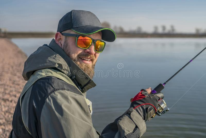 Портрет рыболова Бородатый человек в крышке и солнечных очках держит рыболовную удочку на озере стоковое изображение