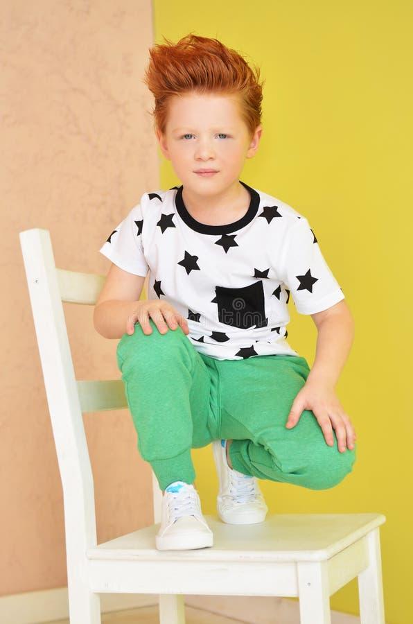 Портрет рыжеволосого непослушного мальчика смотря камеру Милое a стоковая фотография