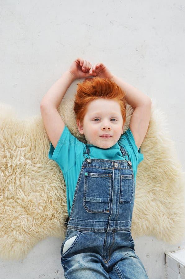 Портрет рыжеволосого непослушного мальчика смотря камеру Милое a стоковое изображение