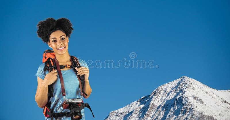 Портрет рюкзака нося и камеры счастливого битника стоя против горы стоковые фото