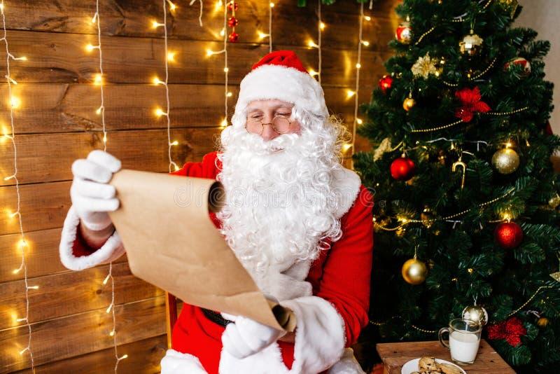 Портрет Санта Клауса сидя на его комнате дома около рождественской елки и большого мешка и читая письмо рождества или стоковые фотографии rf
