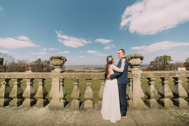 Портрет свадьбы счастливо обнимая стильного жениха и невеста новобрачных представляя на старом каменном парке террасы весной стоковые фото