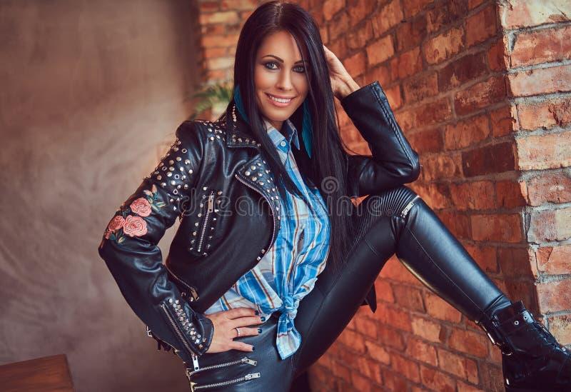 Портрет сексуального брюнет в кожаных джинсах и куртке представляя против кирпичной стены в комнате с интерьером просторной кварт стоковая фотография
