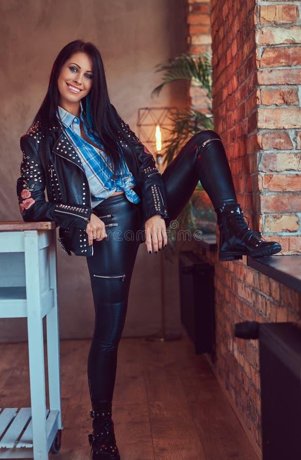 Портрет сексуального очаровательного брюнет представляя в стильной кожаной куртке и джинсах пока полагающся нога на силле окна стоковое изображение