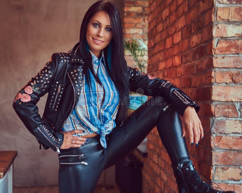 Портрет сексуального очаровательного брюнет представляя в стильной кожаной куртке и джинсах пока полагающся нога на силле окна стоковые изображения rf