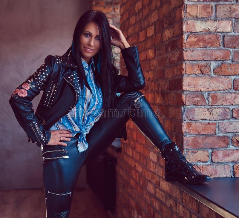Портрет сексуального очаровательного брюнет представляя в стильной кожаной куртке и джинсах пока полагающся нога на силле окна стоковые фото