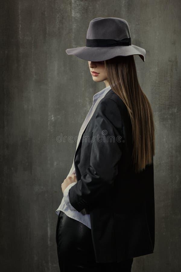 Портрет сексуальной девушки в классической куртке, рубашке и шляпе на его стоковые фото