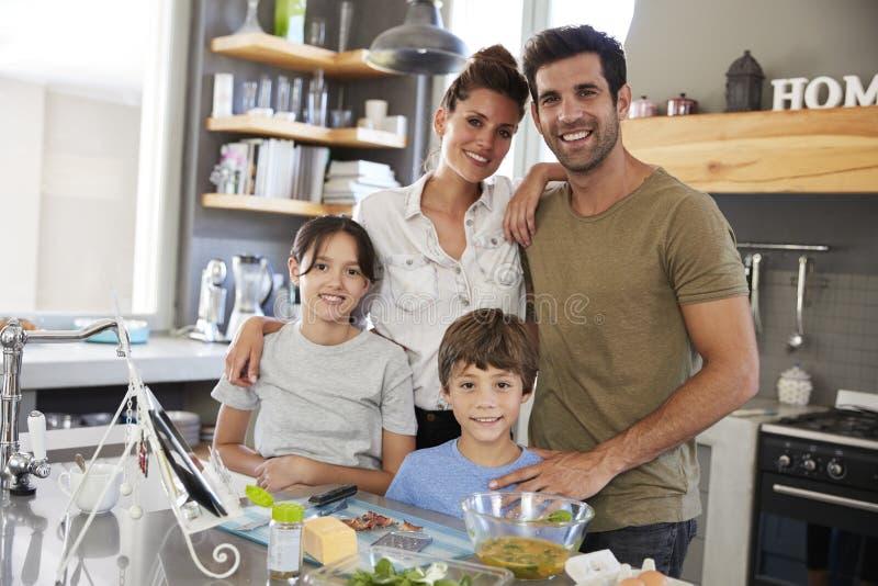 Портрет семьи в кухне после рецепта на таблетке цифров стоковые изображения