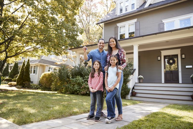 Портрет семьи держа ключи к новому дому на двигать в день стоковое изображение