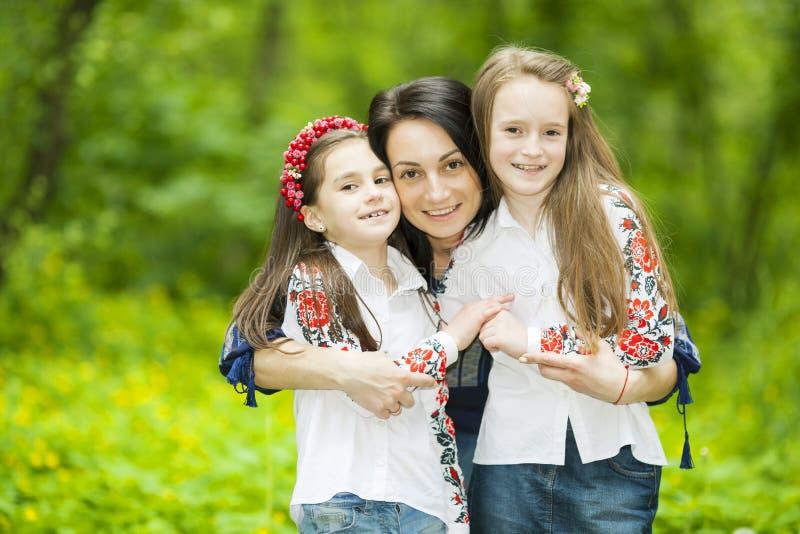 Портрет семьи девушек и матери в парке на предпосылке стоковые фото