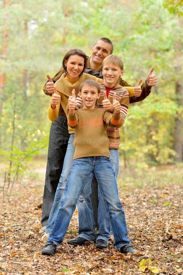Портрет семьи из четырех человек показывая большие пальцы руки вверх в лесе осени стоковые фотографии rf