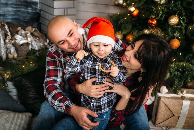 Портрет семьи рождества молодой счастливый усмехаться parents играть с малым ребенк в красной шляпе santa около рождественской ел стоковая фотография rf