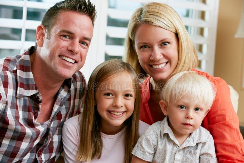 Портрет семьи сидя на софе на дому стоковая фотография