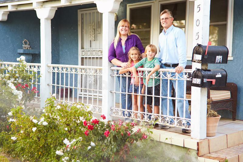 Портрет семьи стоя на крылечке пригородного дома стоковая фотография