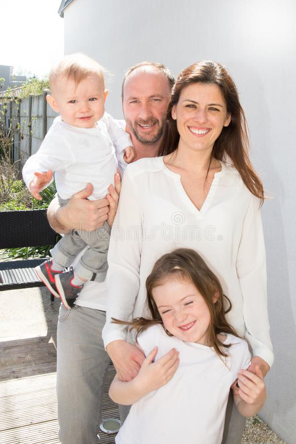 Портрет семьи 4 Счастливые родители внешни с 2 жизнерадостными детьми - белокурым малым мальчиком, девушкой брюнет, стоковое фото