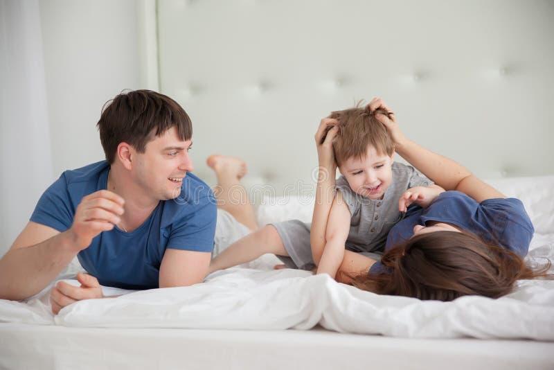 Портрет семьи 3 людей на родителях кладет нося пижамы в постель стоковые фото