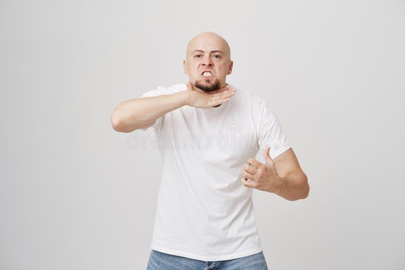 Портрет сердитого надоеданного облыселого человека с бородой показывать если режущ шею, показывая что он подан вверх и прекращен, стоковая фотография