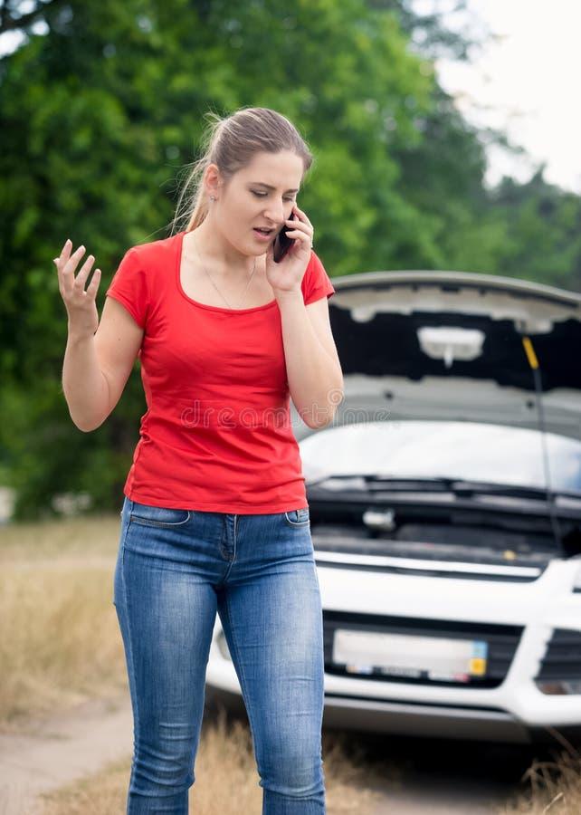 Портрет сердитой молодой женщины говоря телефоном и вызывая помощь к ее сломленному автомобилю в поле стоковое изображение