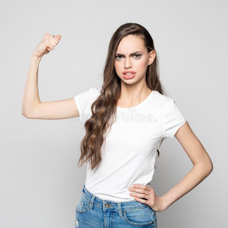 Портрет сердитой молодой женщины изгибая ее мышцу стоковое фото rf