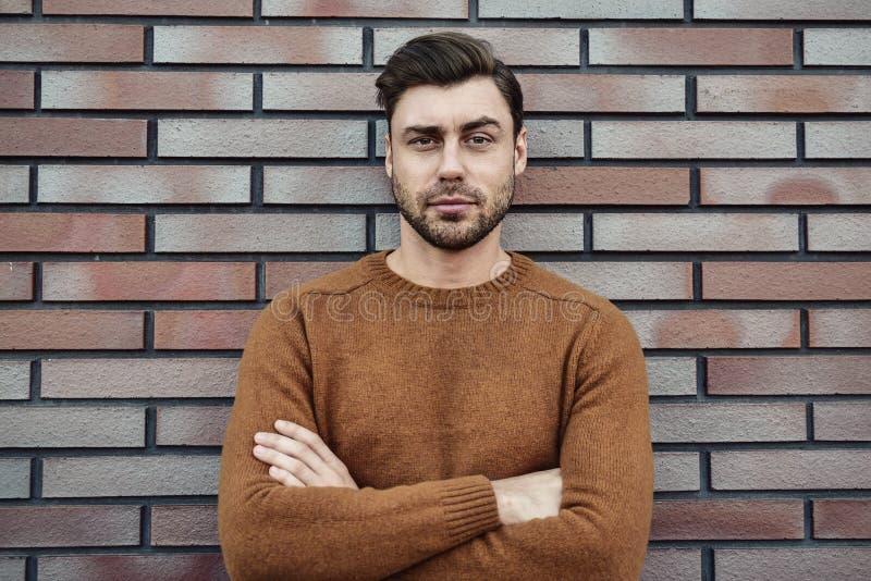 Портрет серьезного мужественного сногсшибательного человека в свитере смотря положение камеры на улице стоковое фото rf
