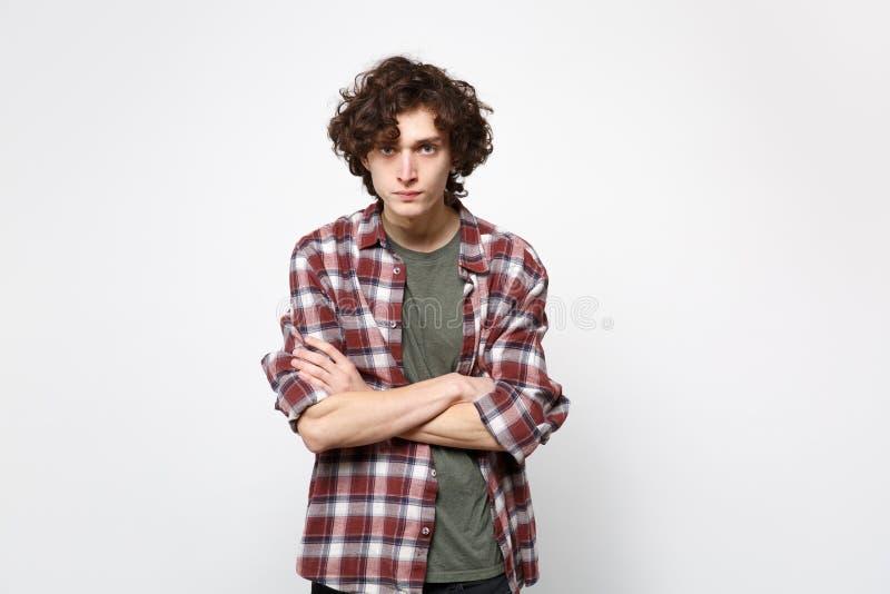 Портрет серьезного строгого молодого человека в случайных одеждах стоя смотрящ руки владением камеры пересек изолированный на бел стоковая фотография rf