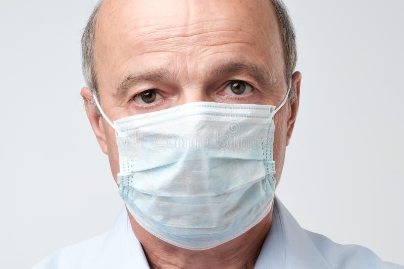 Портрет серьезного человека в специальной маске сотрудник военно-медицинской службы Он смотрит серьезным Mature испытало доктора стоковая фотография