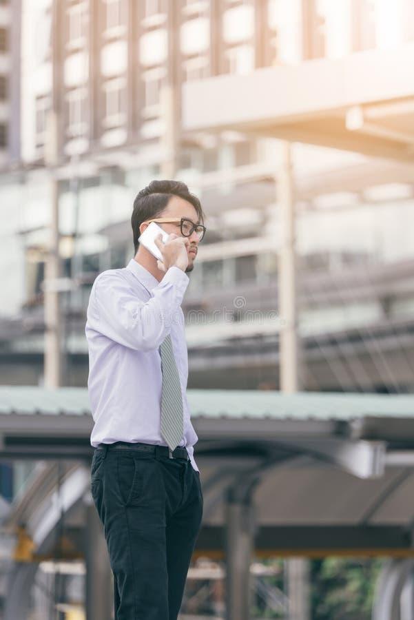 Портрет серьезного человека говоря на smartphone outdoors кавказский бизнесмен используя мобильный телефон, звоня на улице в горо стоковые фотографии rf