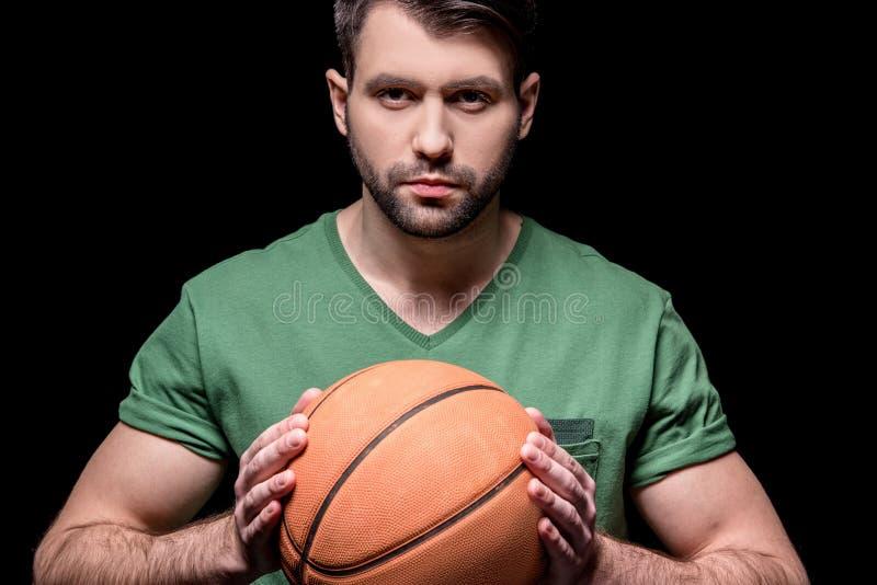 Портрет серьезного человека держа шарик баскетбола в руках стоковая фотография