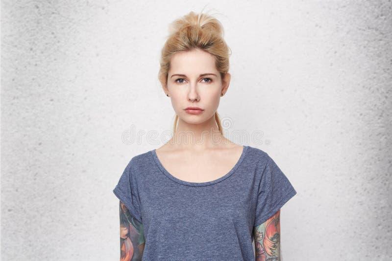 Портрет серьезной белокурой девушки нося голубую футболку, tattoed оружия и прокалыванный нос унылую и confused Она потеряла ее п стоковые изображения