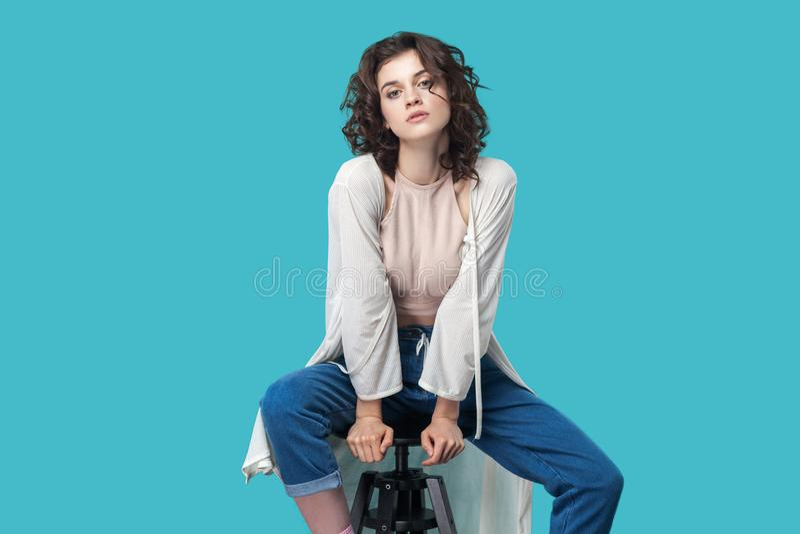Портрет серьезной спокойной красивой молодой женщины брюнета в непринужденном стиле сидя на стуле и смотря камеру с серьезной сто стоковые изображения rf