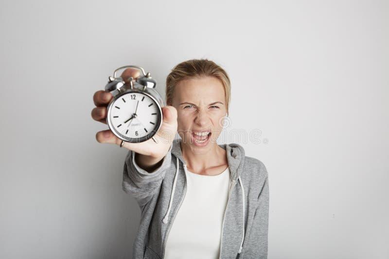 Портрет сердитой женщины держа вахту сигнала тревоги Белое backgroung стоковые фотографии rf