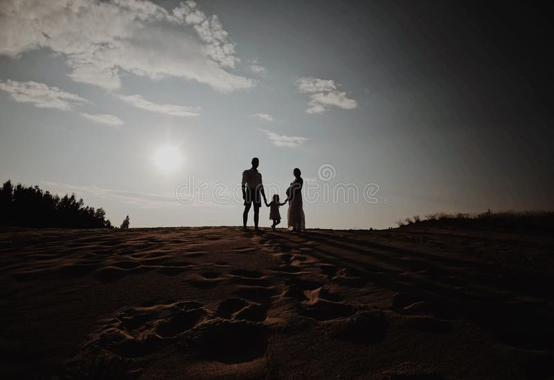 Портрет силуэта красивой молодой семьи в ожидании newborn Человек и женщина стоя лицом к лицу с их стоковое фото