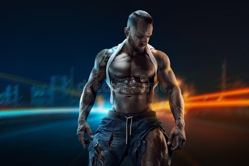 Портрет сильного атлетического человека фитнеса показывая большие мышцы стоковое изображение rf