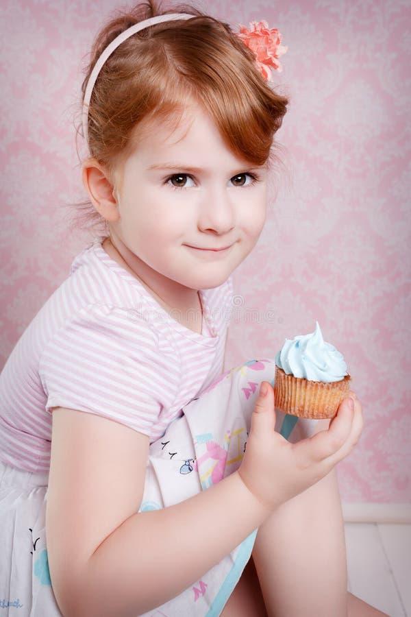 Портрет симпатичной маленькой девочки с пирожным стоковое изображение