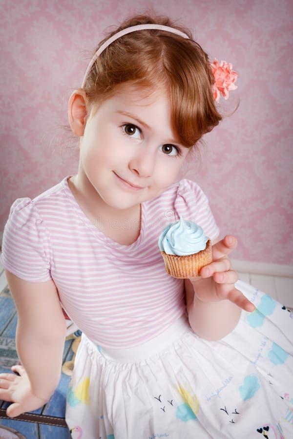 Портрет симпатичной маленькой девочки с пирожным стоковое фото rf