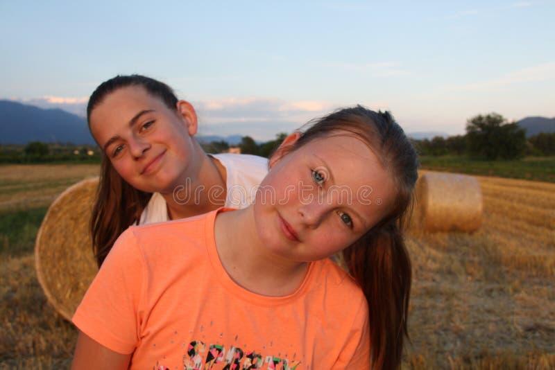 Портрет симпатичных сестер с полем позади стоковое фото