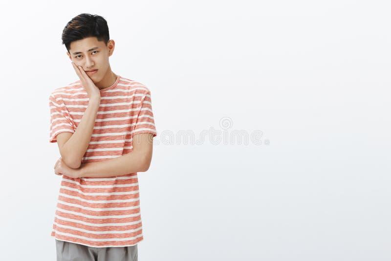 Портрет сиротливой осадки и пробуренный молодой мужской азиатский студент с темной короткой головой склонности стрижки на ладони  стоковая фотография rf