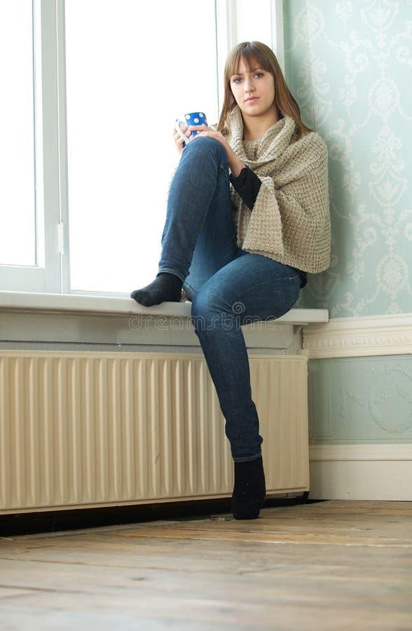 Сиротливая девушка сидя в пустой комнате стоковые фото