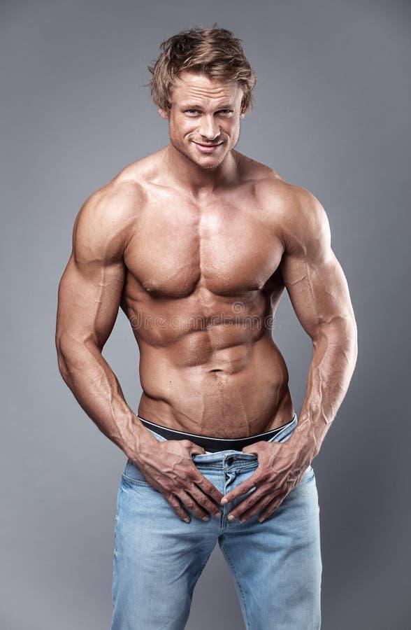 Портрет сильного атлетического человека фитнеса над серой предпосылкой стоковые фото