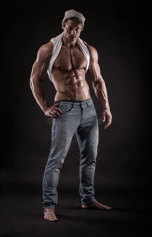Портрет сильного атлетического человека фитнеса над черной предпосылкой стоковое изображение rf