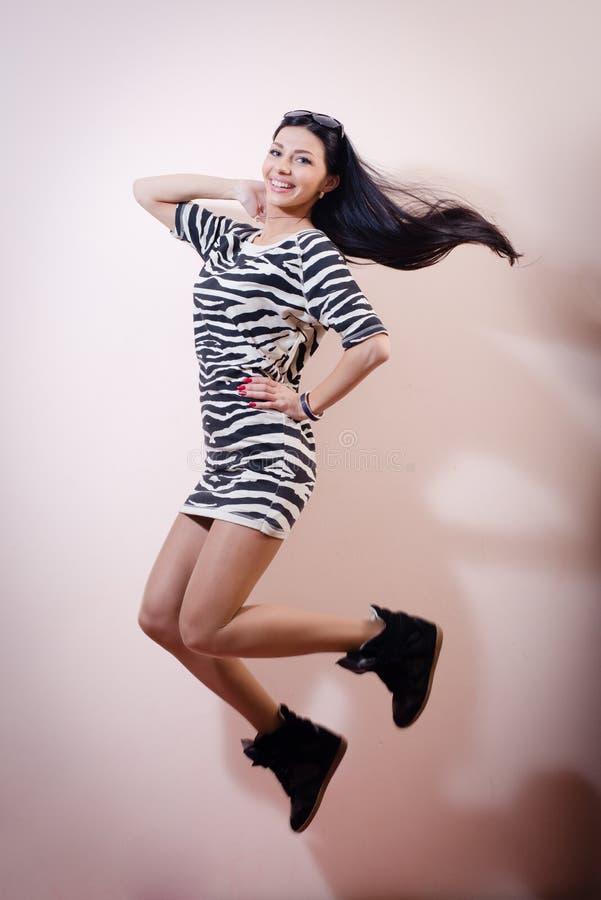 Портрет скакать красивая тонкая молодая женщина брюнет в платье зебры и хихикает счастливая улыбка & смотрящ изображение камеры стоковая фотография