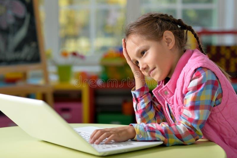 Портрет сконцентрированной маленькой девочки с компьтер-книжкой стоковые фото