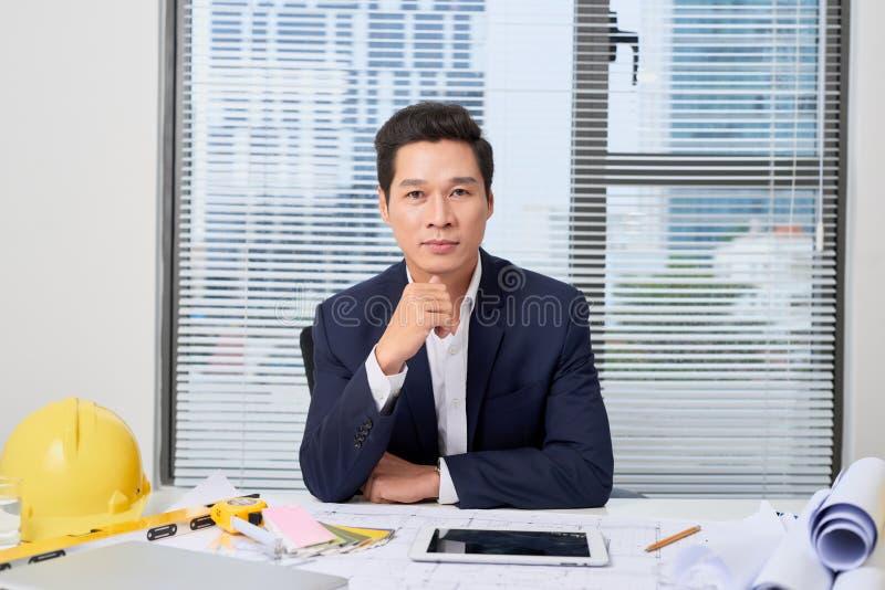 Портрет славного усмехаясь человека, работая дома на некотором проекте, он сидит на белой таблице смотря камеру, писать идеи стоковые фото